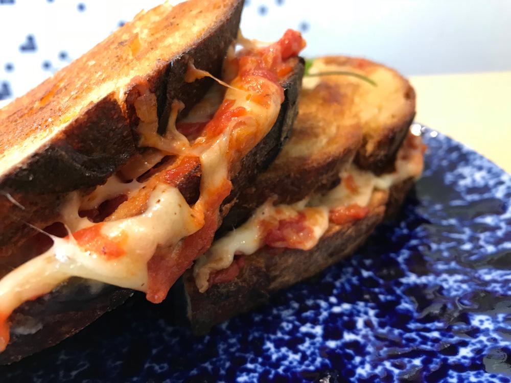 Le grilled cheese est un sandwich chaud fait de pain de campagne toasté au beurre, de fromages divers, de jambon et de sauce tomate.